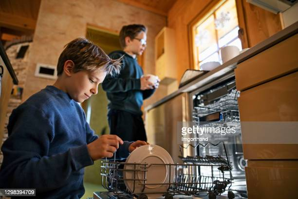 little boys loading the dishwasher - chores stock pictures, royalty-free photos & images
