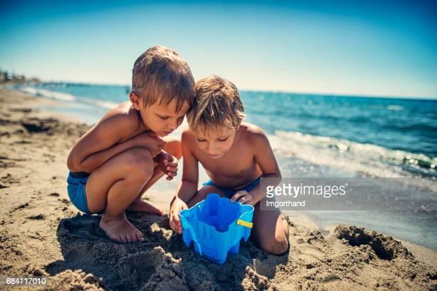 Jongetjes observeren van een vis gevangen in zand emmer