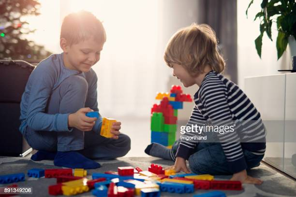 Little boys on christmas morning playing with new blocks on the floor