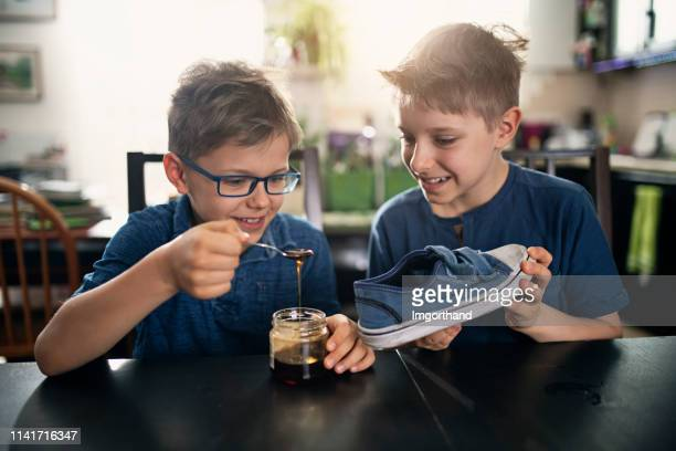 little boys playing an april fools day prank - april fools day stock pictures, royalty-free photos & images