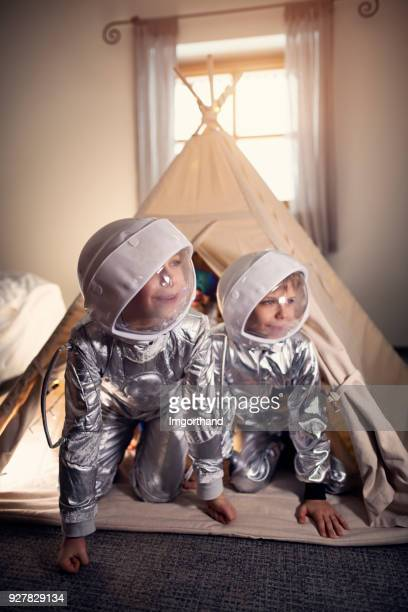 Little boys playing astronauts in their room