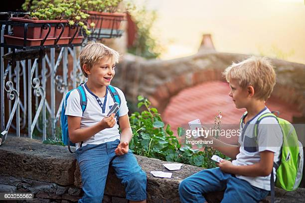 Little boys playing cards on their way to school