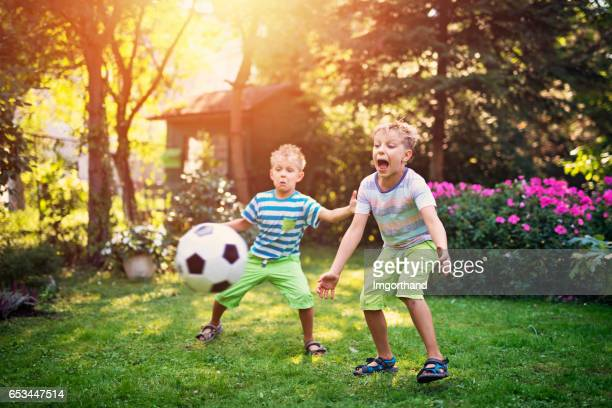 little boys playing football in the garden - sports ball stock pictures, royalty-free photos & images