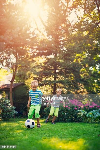 Kleine jongens voetballen in de tuin