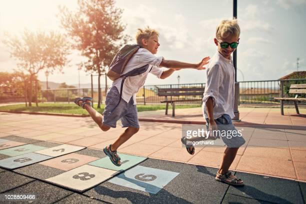 kleine jungs spielen im schulhof - schulhof stock-fotos und bilder
