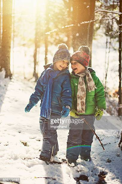 Little boys playing in winter forest