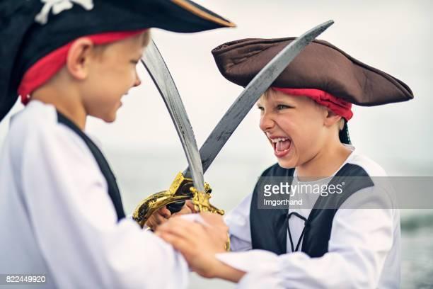 Les petits garçons jouer pirates sur une plage