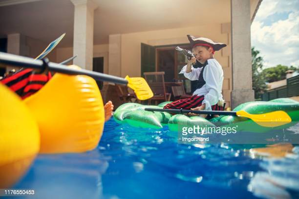 little boys playing pirates - kids pool games stock pictures, royalty-free photos & images