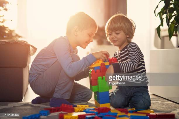 Little boys playing with blocks on the floor at home