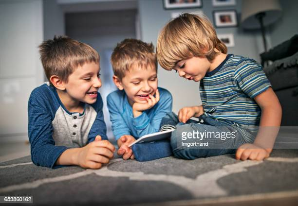 little boys playing with digital tablet at home - brother stock pictures, royalty-free photos & images