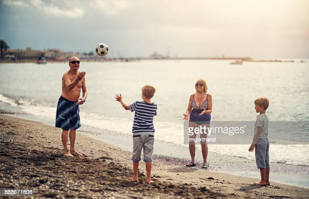 Little boys playing with grandparents on beach