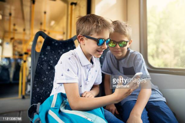little boys riding to school by public transport - imgorthand stock photos and pictures