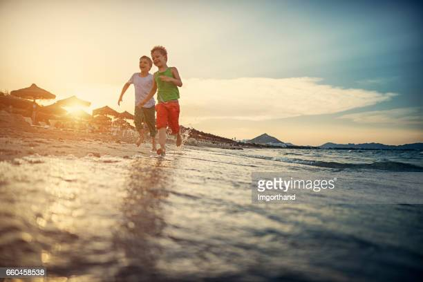 little boys running happily on the beach - balearics stock pictures, royalty-free photos & images