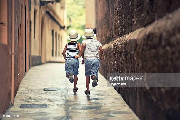 Little boys running in a narrow street of Palma