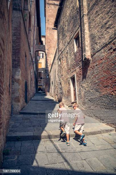 little boys running in the narrow streets of siena, italy - siena italy stock pictures, royalty-free photos & images