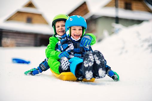 Little boys sliding on sled in winter 597643920