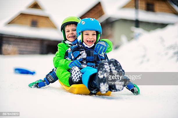 little boys sliding on sled in winter - sports helmet stock pictures, royalty-free photos & images