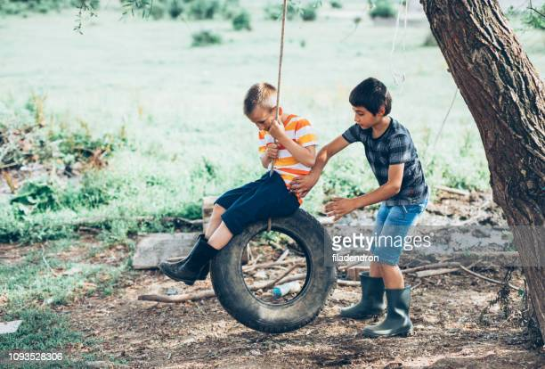 little boys swinging on a tire - doing a favor stock pictures, royalty-free photos & images