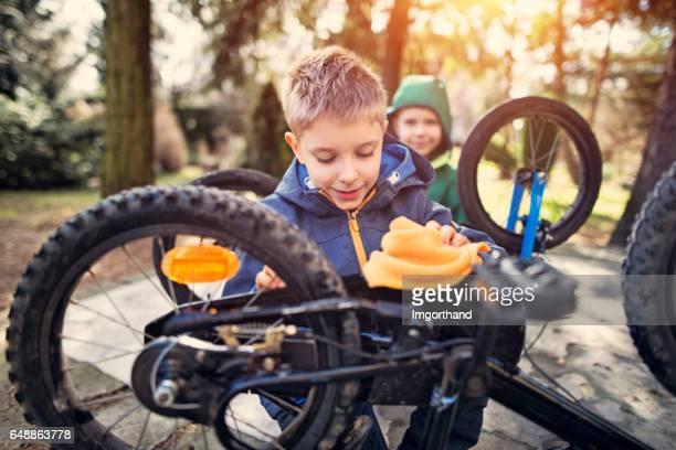 Jongetjes die neigt om hun fietsen na winter
