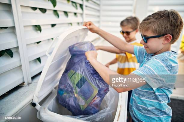little boys throwing out segregated trash to garbage bins - absence stock pictures, royalty-free photos & images