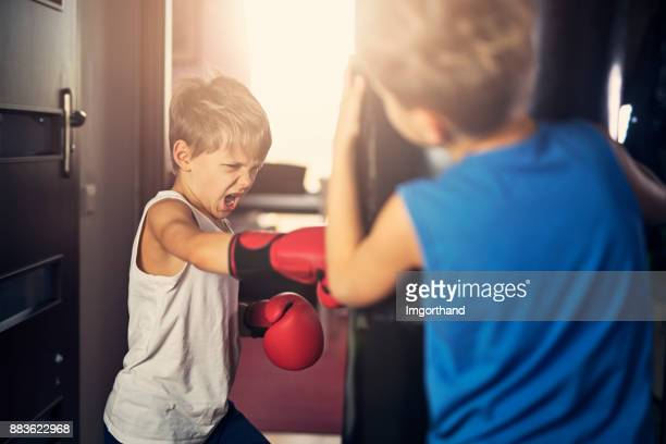 Little boys training boxing with punching bag