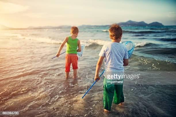 Kleine Jungs, die versuchen, die Fische im Meer fangen