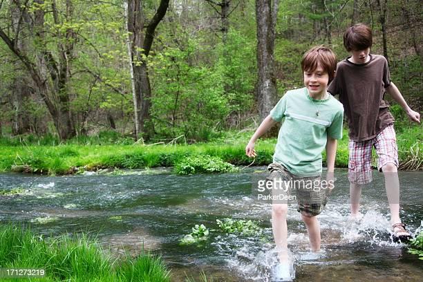 Little Boys Walking Splashing in Stream- Wooded Green Park