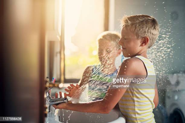 little boys washing hands and playing with water - lavandino foto e immagini stock