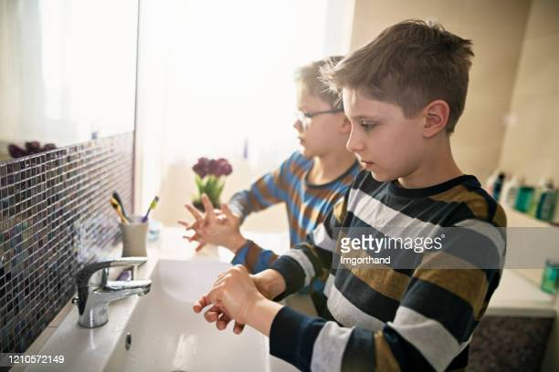 little boys washing hands thoroughly - illness prevention stock pictures, royalty-free photos & images