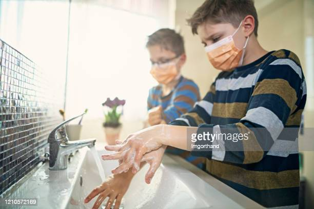 little boys wearing face masks washing hands thoroughly - handwashing stock pictures, royalty-free photos & images