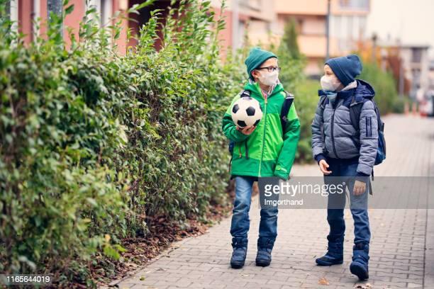 little boys wearing pollution masks going to school - maschera di protezione da lavoro foto e immagini stock