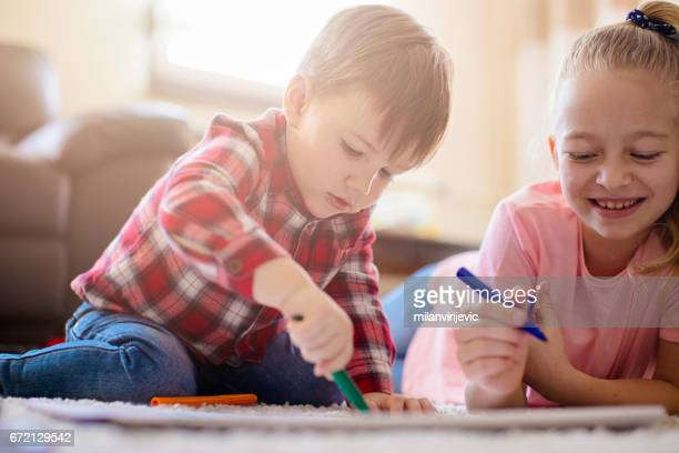 Little brother and sister drawing together