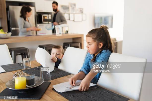 """little brother and sister helping to set the table at lunch time. - """"martine doucet"""" or martinedoucet stock pictures, royalty-free photos & images"""