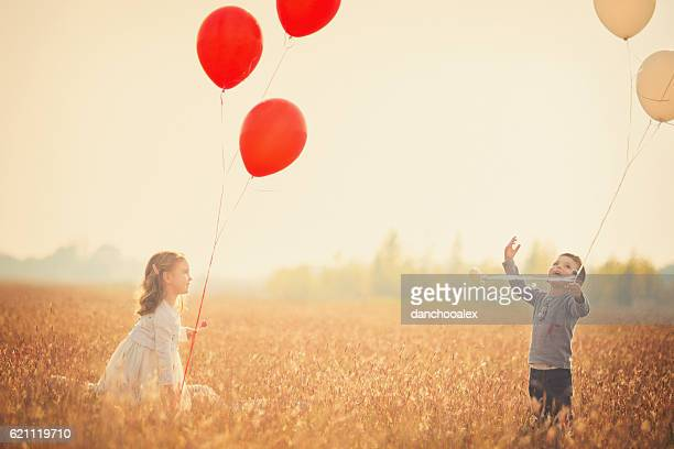 Little brother and sister plating with balloons