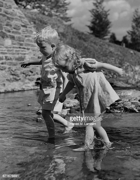 little brother and sister walking in water holding hands - {{ collectponotification.cta }} foto e immagini stock