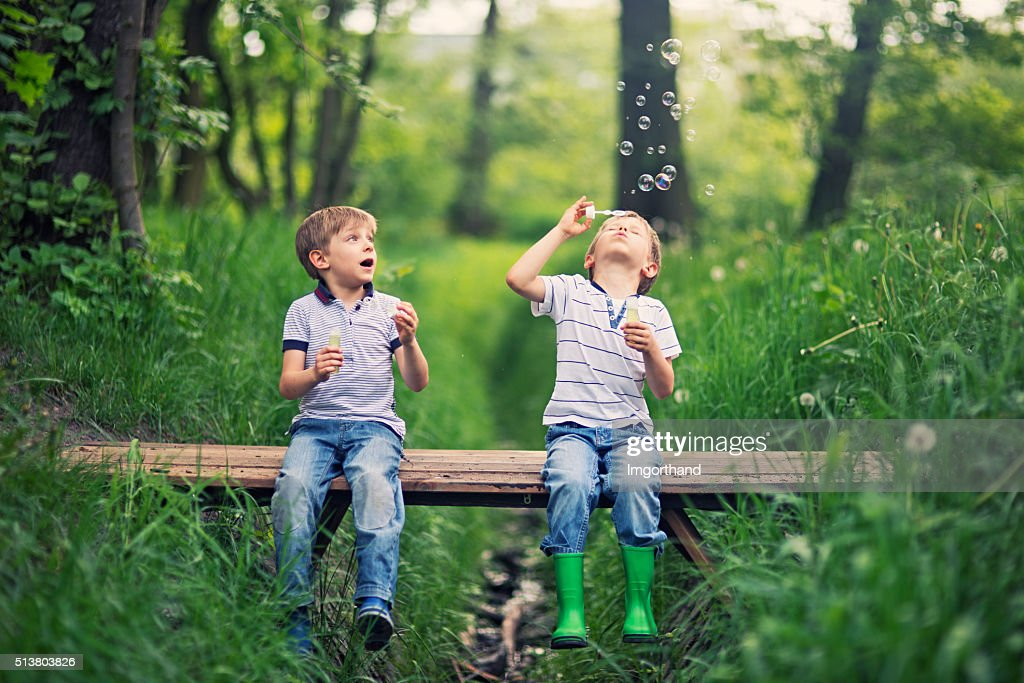 Little brother blowing  bubbles on a little bridge in forest : Stock Photo