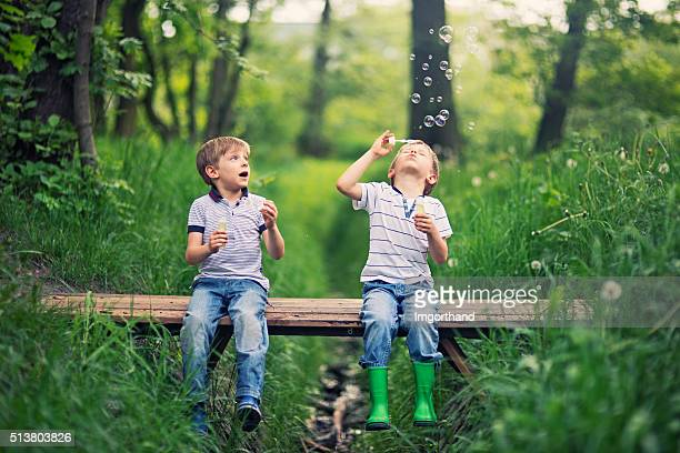 little brother blowing  bubbles on a little bridge in forest - spring flowing water stock pictures, royalty-free photos & images