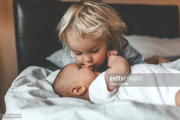 little brother hugging his newborn sister. toddler kid meeting new sibling. cute boy and new born baby girl relax in a white bedroom. family with children at home. love, trust and tenderness - b��ro stock-fotos und bilder