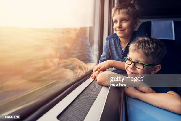 little brotheres enjoying travelling by train - train stock photos and pictures