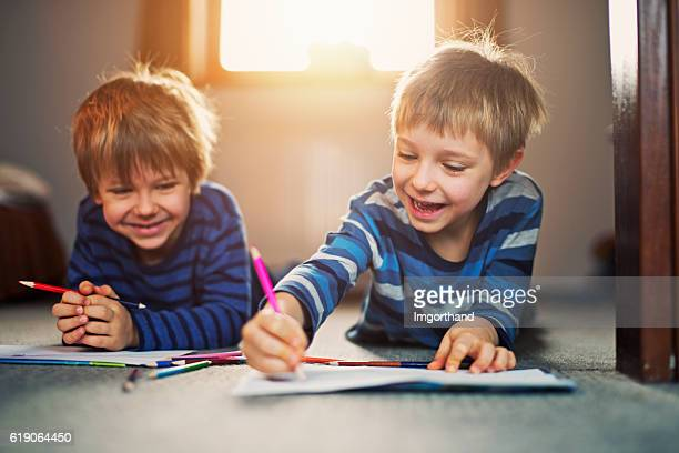 little brothers enjoying drawing on the floor - colouring stock photos and pictures