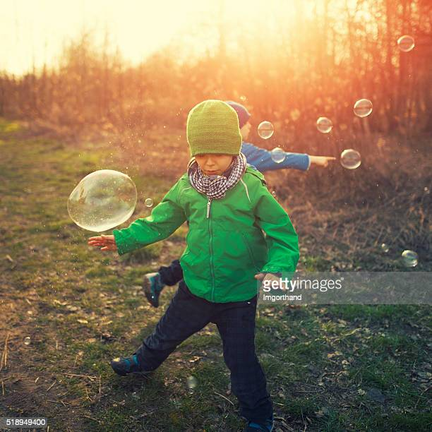 Petits frères s'amuser avec des bulles sur le début du printemps en soirée