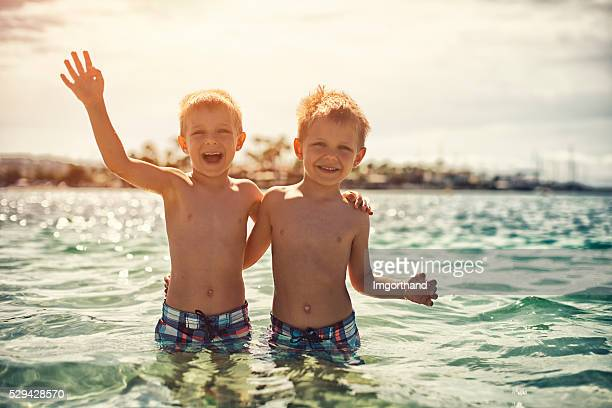 Little brothers in the sea waving to the camera.