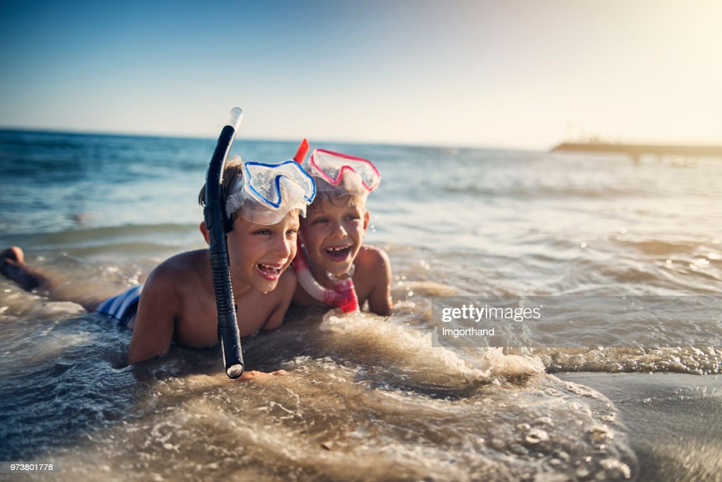 Little brothers lying on beach after snorkeling : Stock Photo