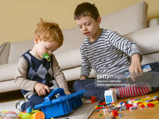Little brothers (2 and 7 years) play together at home