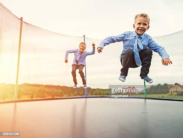 jüngeren brüder tragen anzug springen auf trampolin - bruder stock-fotos und bilder