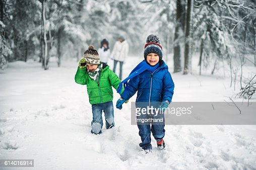 Little brothers with family enjoying winter walk in forest.