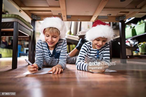 Little brothers writing letters to santa clasu