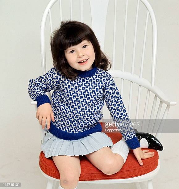 A little brownhaired girl perched on a white openback chair with a red cushion wearing black patentleather shoes white kneesocks a light blue pleated...