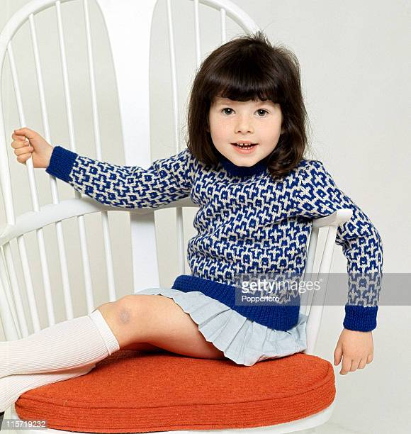 A little brownhaired girl seated on a white openback chair with a red cushion wearing white kneesocks a light blue short pleated skirt and a blue and...