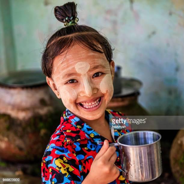 little burmese girl  drinking water in village near bagan, myanmar - myanmar stock pictures, royalty-free photos & images